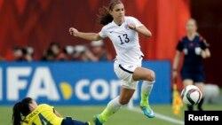 La estadounidense Alex Morgan (13) supera la marca de la colombiana Nataly Arias durante el juego del Mundial femenino en Edmonton, Alberta, en el que Estados Unidos pasó a cuartos de final.