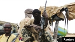 FILE - Militiaman from the Ansar Dine Islamic group sit on a vehicle in Gao, in northeastern Mali, June 18, 2012.