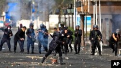 Seorang wanita Mesir berlari mencari tempat berlindung saat polisi anti huru-hara melemparkan batu di dekat gedung keamanan pemerintah setempat di Port Said (Foto: dok). Bentrokan polisi-pengunjuk rasa terus berlangsung, sementara pengadilan Mesir mempertahankan hukuman mati atas 21 terdakwa kasus kerusuhan sepakbola di wilayah ini.