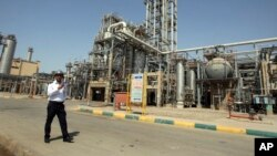 FILE - In this 2011 file photo, an Iranian security guard stands at the Maroun Petrochemical plant at the Imam Khomeini port, southwestern Iran. U.S. companies are interested in developing markets in Iran.