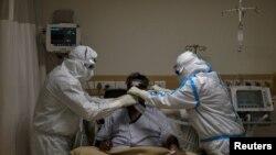 အိႏၵိယႏိုင္ငံ New Delhi ၿမိဳ႕ရွိ ေဆးရံုတခုမွာ COVID 19 လူနာ တဦးကို PPE ၀တ္စံု၀တ္ထားၿပီး ကုသေပးေနတဲ့ က်န္းမာေရး၀န္ထမ္းမ်ား။ (ေမ ၂၈၊ ၂၀၂၀)