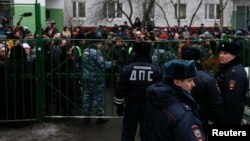 Interior Ministry members stand guard as bystanders and relatives of students gather behind a fence near a high school, where a student fatally shot a teacher and a police officer dead, on the outskirts of Moscow, Feb. 3, 2014.