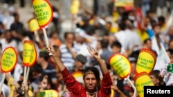 "FILE - A Kurdish woman holds a sign that reads ""Don't ban my language"" during a rally in Diyarbakir, Turkey, Sept. 1, 2009."