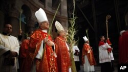 Christian clergymen carry palm fronds during the Palm Sunday procession in the Church of the Holy Sepulcher, traditionally believed by many to be the site of the crucifixion, in Jerusalem's Old City, March 20, 2016.