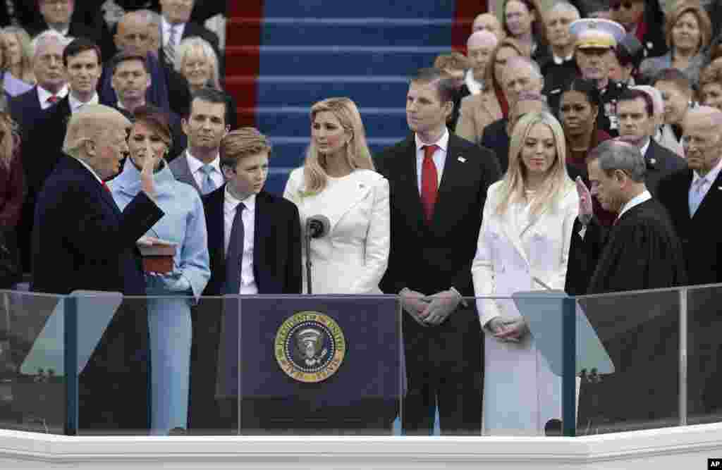Donald Trump is sworn in as the 45th president of the United States by Chief Justice John Roberts as Melania Trump and his family looks on during the 58th Presidential Inauguration at the U.S. Capitol in Washington, Jan. 20, 2017.