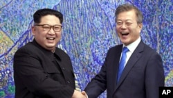 Lideri Severne i Južne Koreje, Kim Džong Un i Mun Džae-in rukuju se tokom sastanka u demilitarizovanoj zoni, 27. april 2018.