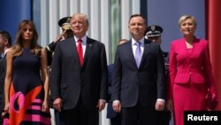 U.S. President Donald Trump stands next to First Lady Melania Trump, Polish President Andrzej Duda and Polish First Lady Agata Kornhauser-Duda before his public speech at Krasinski Square, in Warsaw, Poland July 6, 2017. REUTERS/Carlos Barria - RTX3AADZ