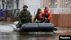 Canadian soldiers and a city official check on residents in a flooded residential area in Gatineau, Quebec, Canada, May 8, 2017.
