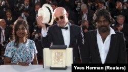 """Sutradara film """"Dheepan"""", Jacques Audiard (tengah), bersama aktris Kalieaswari Srinivasan (kiri) dan aktor Jesuthasan Antonythasan berpose setelah """"Dheepan"""" memenangkan film terbaik di festival film Cannes, Perancis hari Minggu (24/5)."""