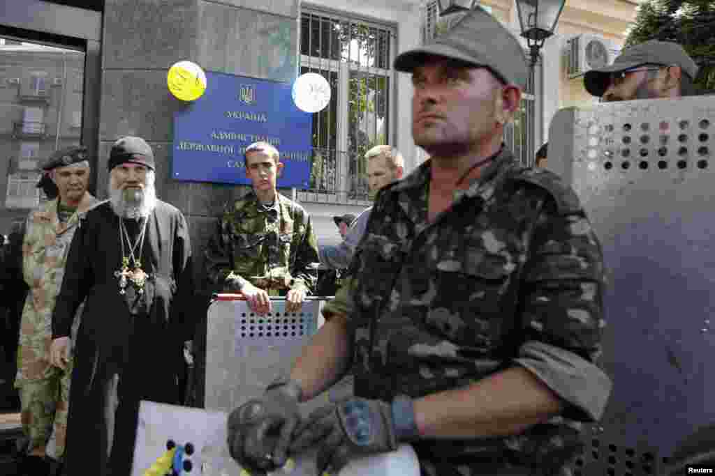 Maidan self-defence activists take part in a protest outside the headquarters of the National Border Guard in Kyiv, June 12, 2014.