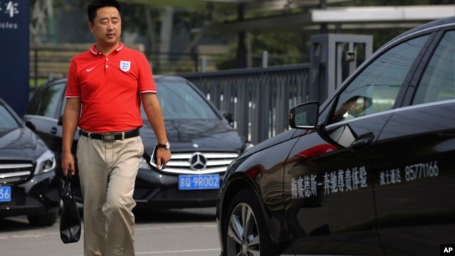 A man walks past Mercedes-Benz cars parked outside the dealer sales showroom in Beijing, China, Aug. 18, 2014.