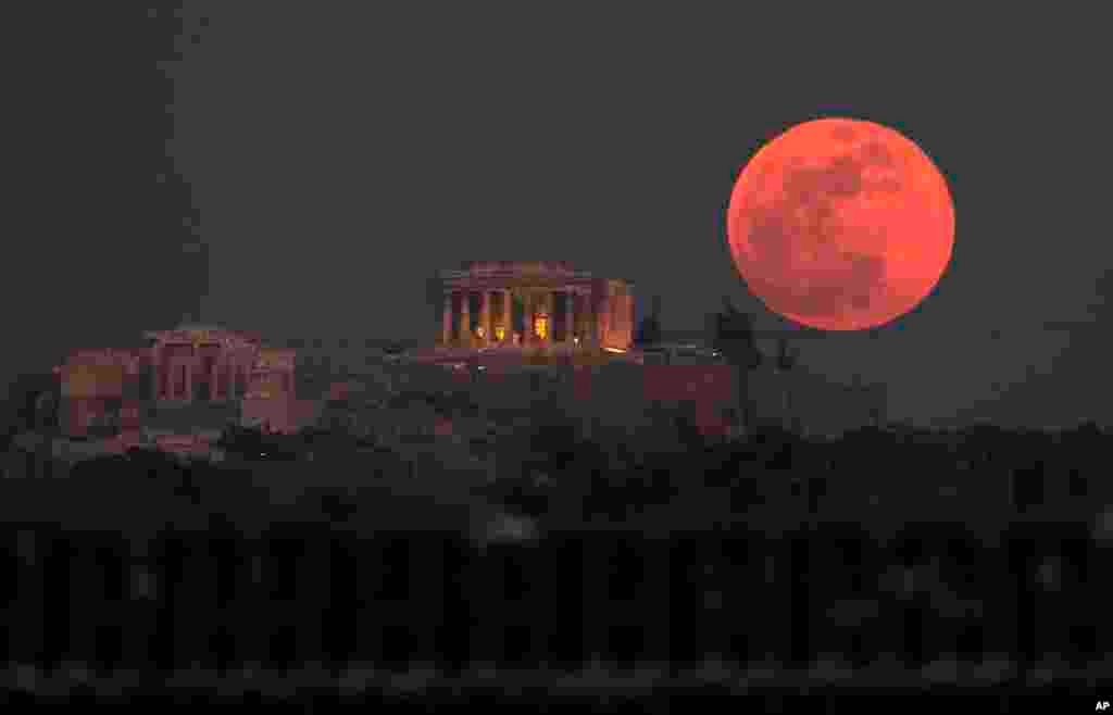 A super blue blood moon rises behind the 2,500-year-old Parthenon temple on the Acropolis of Athens, Greece.