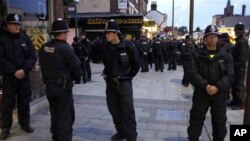Police officers form a cordon around a group of local people on Eltham High Street in London, Wednesday, Aug. 10, 2011. A large group of local men gathered in the area on Wednesday to deter looters and a large number of police officers was also present to