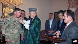 A handout photo shows Afghan President Hamid Karzai awarding a medal to outgoing International Security Assistance Force (ISAF) commander General David Petraeus at the Presidential Palace in Kabul, July 18, 2011