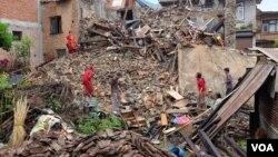 受地震影響的家庭在瓦礫中找物品。
