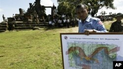 In this photo taken Nov. 7, 2008, a Cambodian deminer, holds a map of a disputed border at an entrance of Cambodia's Preah Vihear temple in a world heritage site near the Cambodian-Thai border.