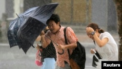 People holding umbrellas walk against strong winds and heavy rain brought by Typhoon Neoguri on a street in Naha, on Japan's southern island of Okinawa, July 9, 2014.