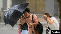 9일 일본 오키나와 섬 주민들이 태풍을 피해 우산을 움켜쥐고 있다.