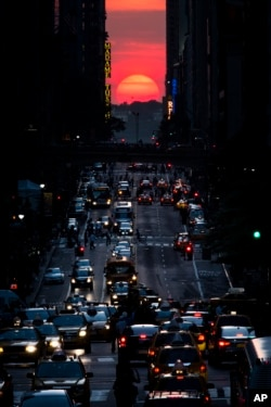 FILE - The sun sets along 42nd Street in Manhattan on May 29, 2013, in New York. (AP Photo/John Minchillo)