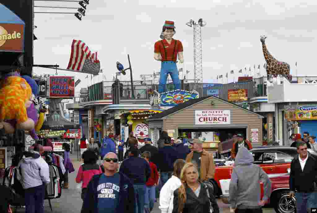 In this Oct. 13, 2013 photo, people walk along the rebuilt boardwalk in Seaside Heights, N.J. A year ago the boardwalk was destroyed and the area was inundated by sand in the wake of Superstorm Sandy.
