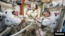 NASA astronauts Reid Wiseman (R) and Barry Wilmore work inside the International Space Station on October 1, 2014.