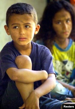 Anak-anak tunawisma Mesir duduk di trotoar di sebuah jalan di Kairo, 20 Agustus 2004. (Foto: Reuters)
