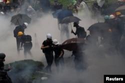 AManifestantes contra la ley de extradición están rodeados de gases lacrimógenos durante los enfrentamientos con la policía en Tsuen Wan en Hong Kong, el 25 de agosto de 2019.