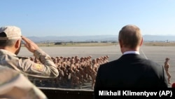 Tổng thống Nga Vladimir Putin (phải) nhìn binh sĩ diễu hành khi ông và Tổng thống Syria Bashar al-Assad thăm căn cứ không quân Hemeimeem ở syria, ngày 12 tháng 12, 2017.