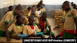 FILE - Students learn with the help of a computer tablet provided by UNICEF at a school in Baigai, northern Cameroon, Tuesday 31 October 2017.