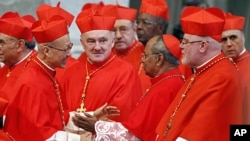 Newly-appointed cardinal John Tong, of Hong Kong, left, is congratulated by other cardinals after being elevated in St. Peter's Basilica at the Vatican, February 18, 2012.
