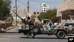 A Houthi Shiite rebel mans a machine gun mounted on a military truck in Sanaa, Yemen, Oct. 20, 2014.