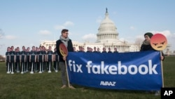 Avaaz campaigners hold a banner in front of 100 cardboard cutouts of Facebook CEO Mark Zuckerberg outside the U.S. Capitol in Washington, April 10, 2018, ahead of his Senate testimony.