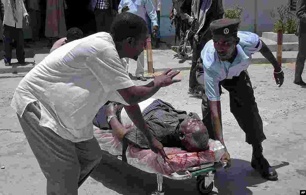 Somalis stretcher away a man wounded in a blast at the national theater. (AP)