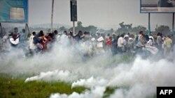 Des partisans de l'opposition accueillis par des tirs de gaz lacrymogène, à Kinshasa, le 26 nov. 2011