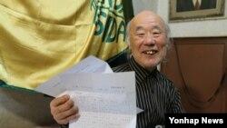 이산가족상봉 대상자로 확정된 김우종(87) 할아버지가 8일 서울 광진구 화양동 자택에서 최종상봉자 확인서를 살펴본 뒤 환하게 웃고 있다.