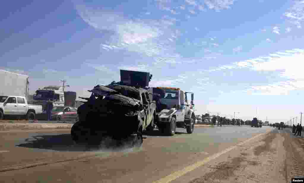 A police vehicle is towed after a suicide bomb attack in Taji, Iraq, Feb. 5, 2013.