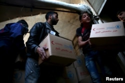 FILE - Men unload aid boxes from a Red Crescent aid convoy in the rebel held besieged town of Jesreen, in the eastern Damascus suburb of Ghouta, Syria, March 7, 2016.