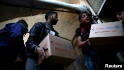 file - Men unload aid boxes from a Red Crescent aid convoy in an eastern Damascus suburb, March 7, 2016.