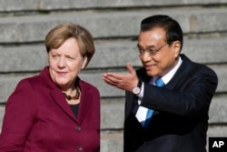 Chinese Premier Li Keqiang, right, shows the way for German Chancellor Angela Merkel during a welcome ceremony held outside the Great Hall of the People in Beijing, China, Oct. 29, 2015.