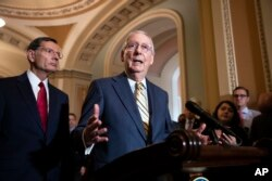 Senate Majority Leader Mitch McConnell, R-Ky., joined at left by Sen. John Barrasso, R-Wyo., speaks to reporters about the political battle for confirmation of President Donald Trump's Supreme Court nominee, Brett Kavanaugh.