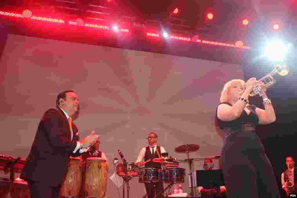 El cantante puertorriqueño Gilberto Santa Rosa disfruta de la interpretación de una integrante de su orquesta a ritmo de trompeta.