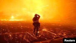 Fotografer kebakaran Tod Sudmeier terkena terpaan angin kencang saat bara api membakar kawasan Solimar di Ventura County, California, 26 Desember 2015. (Foto: dok).