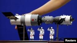 資料照: 在酒泉衛星發射中心展示的中國神舟9號飛船與三名中國宇航員的模型。 (2012年6月15日)