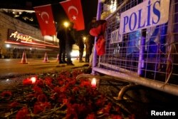Flowers are placed in front of a police barrier near the entrance of Reina nightclub by the Bosphorus, which was attacked by a gunman, in Istanbul, Turkey, Jan. 1, 2017.