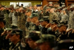 "FILE - U.S. and Philippine troops salute during the opening ceremony of their joint military exercise dubbed ""Balikatan 2015"" at Camp Aguinaldo at suburban Quezon city, northeast of Manila, Philippines, April 20, 2015."