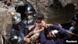 Para petugas mengangkat anak perempuan yang diselamatkan dari reruntuhan bangunan yang ambruk di Mumbai, India (27/9).