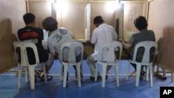 Seorang perempuan berkonsultasi dengan suaminya saat akan mengisi surat suara dalam Pemilu Sela di salah satu TPS, di Filipina (13/5).