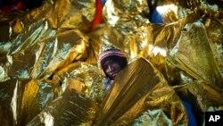 Dembo Nyasi, 22 ans, de Gambie, se couvre d'une couverture chauffante au pont du bateau Golfo Azzurro après avoir été sauvé par des membres de l'ONG Proactive Open Arms, en Méditerranée, à environ 24 miles au nord de Sabratha en Libye.