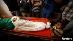 Palestinian boy stands next to the bodies of the wife of Hamas's military leader, Mohammed Deif, and his infant son Ali, whom medics said were killed in Israeli air strikes, during their funeral in the northern Gaza Strip August 20, 2014. Israeli air stri