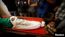 Palestinski dečak kraj tela supruge i deteta lidera Hamasa Mohameda Deifa tokom sahrane